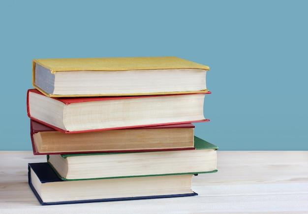 Pilha de livros em capas de cor em cima da mesa.