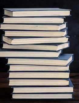 Pilha de livros em uma capa azul em uma mesa de madeira marrom