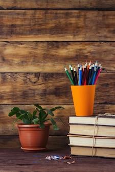 Pilha de livros, lápis de cor em um copo de plástico, flor em uma panela e costeleta de lápis de cor sobre um fundo de madeira
