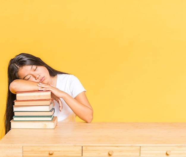 Pilha de livros na mesa e mulher dormindo