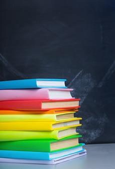 Pilha de livros no fundo do quadro de professores