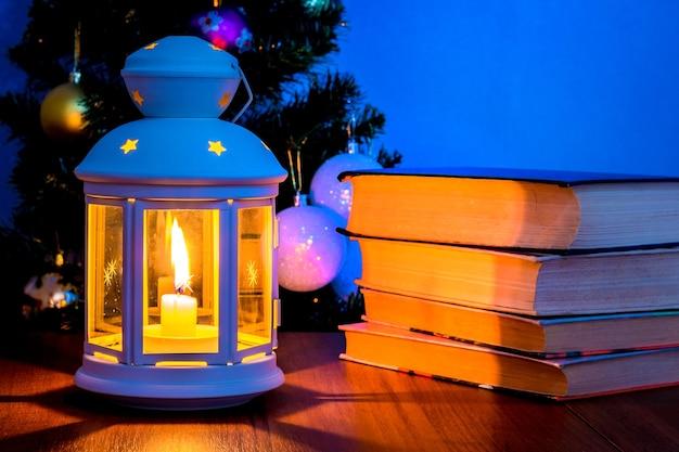 Pilha de livros perto da lanterna com vela e árvore de natal_