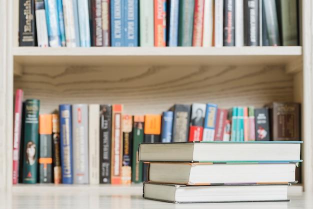 Pilha de livros perto de estante de livros na biblioteca