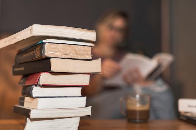 Pilha de livros perto de ler mulher e café
