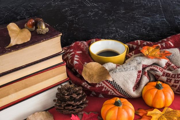 Pilha de livros perto de símbolos de bebida e outono