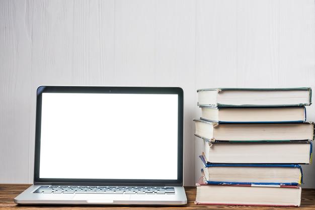Pilha de livros perto do laptop