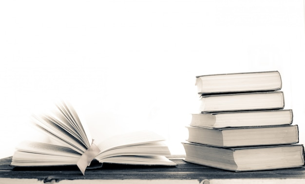 Pilha de livros raros. livro aberto, livros de capa dura na mesa de madeira.