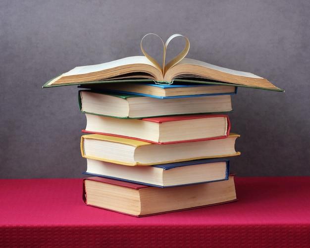 Pilha de livros sobre a mesa com uma toalha de mesa vermelha.
