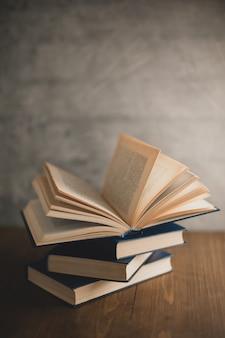Pilha de livros sobre uma mesa de madeira e no fundo da parede de concreto cinza