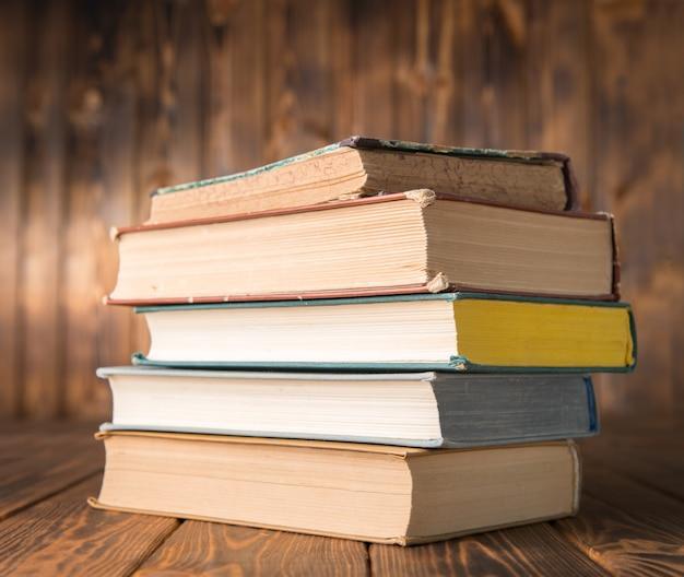 Pilha de livros sobre uma mesa de madeira