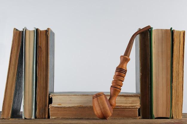 Pilha de livros velhos, cachimbo na prateleira de madeira contra a parede branca