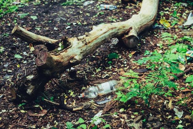 Pilha de lixo na floresta entre plantas. plástico tóxico para a natureza em todos os lugares. pilha de lixo no parque entre a vegetação.