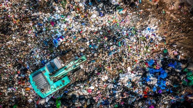 Pilha de lixo na lixeira ou aterro, caminhões de lixo de vista aérea descarregam lixo para um aterro, o aquecimento global.