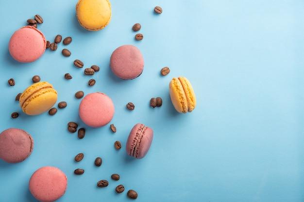 Pilha de macaron colorido francês ou italiano e grão de café na mesa azul