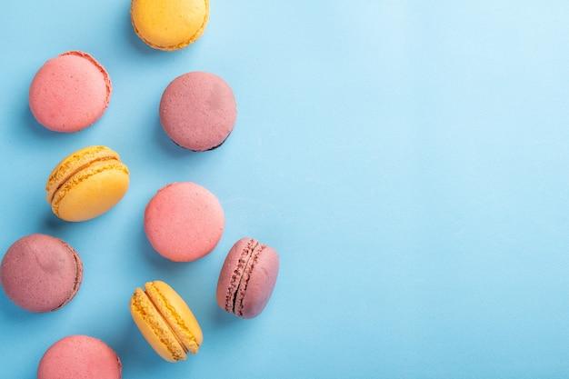 Pilha de macaron francês ou italiano colorido na mesa azul com vista superior da superfície