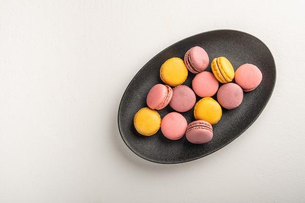Pilha de macaron francês ou italiano colorido na placa escura colocada na mesa branca com para