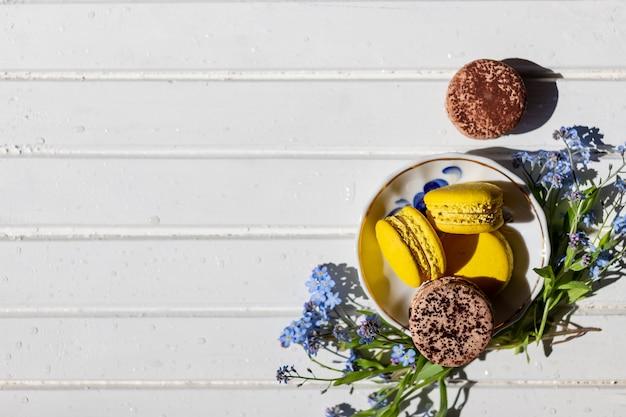 Pilha de macarons franceses ou italianos coloridos na chapa branca, colocar na mesa de madeira