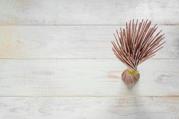 Pilha de macarrão cru soba na mesa de madeira whte. comida japonesa tradicional. vista do topo.