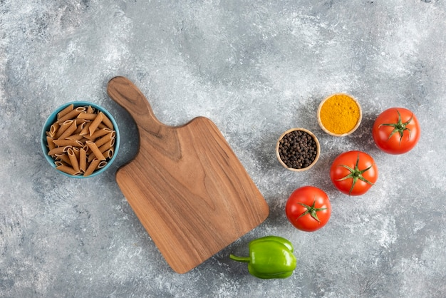 Pilha de macarrão dietético marrom sobre fundo cinza com vegetais e especiarias.