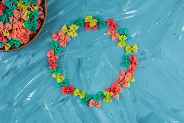 Pilha de macarrão farfalle cru colorido sobre fundo azul.