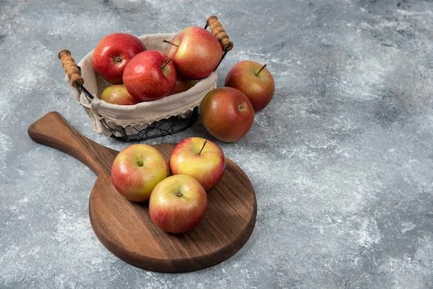Pilha de maçãs frescas maduras na placa de madeira e na cesta.