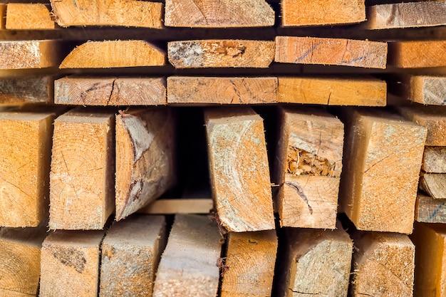 Pilha de madeira serrada de construção no canteiro de obras com profundidade de campo estreita. barras de madeira.