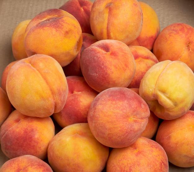 Pilha de maduros pêssegos redondos amarelos-vermelhos