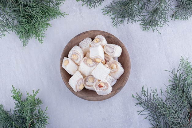 Pilha de manjar turco e ramos de pinheiro em fundo branco.