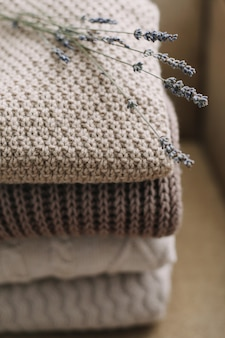 Pilha de mantas de lã sobre um fundo claro. tecidos de diferentes padrões dispostos em camadas. pilha de roupas de malha (camisolas, cachecóis, pulôveres).