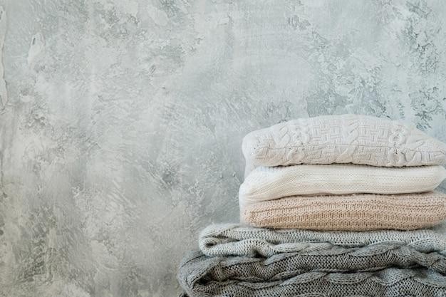 Pilha de mantas e mantas de malha em fundo cinza surrado. decoração de casa aconchegante e calorosa