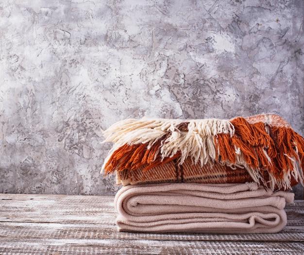 Pilha de mantas na luz de fundo de madeira