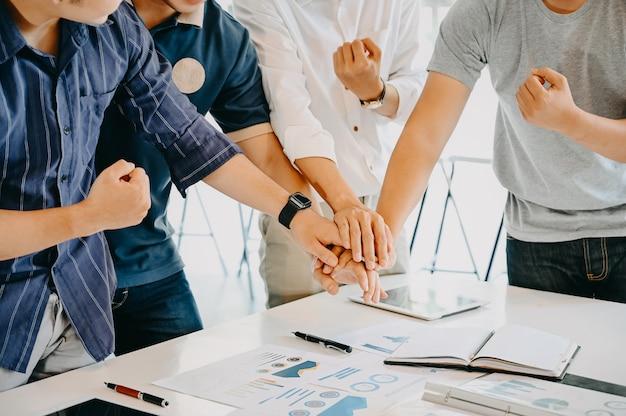 Pilha de mãos conceito de unidade e trabalho em equipe; executivos que unem suas mãos na mesa de escritório.