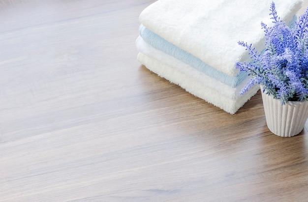 Pilha de maquete de toalhas brancas e planta de casa na mesa de madeira com espaço de cópia.
