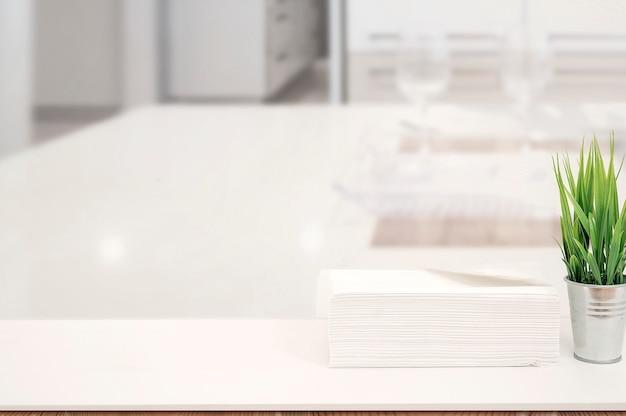 Pilha de maquete de toalhas de papel na mesa branca dentro de casa com espaço de cópia