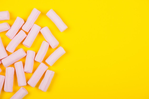Pilha de marshmallows rosa em um fundo amarelo