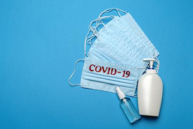 Pilha de máscaras faciais médicas descartáveis azuis com sinal covid-19 e desinfetante para as mãos com álcool anti-séptico sobre fundo azul