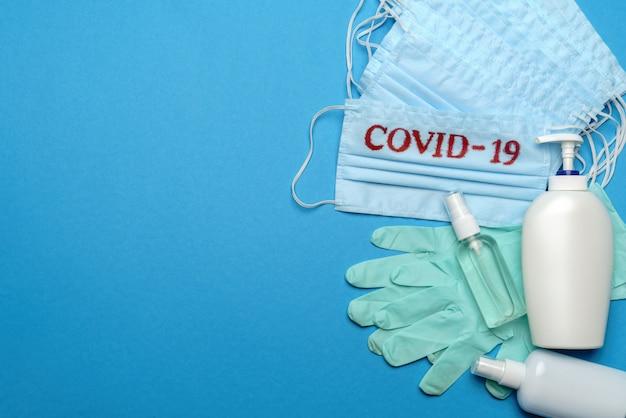 Pilha de máscaras faciais médicas descartáveis azuis com sinal covid-19, luvas de látex de borracha e desinfetante para as mãos com álcool anti-séptico em fundo azul