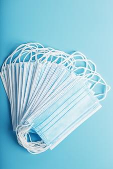 Pilha de máscaras médicas protetoras em uma mesa azul, isolada. proteção contra doenças, vírus e bactérias, coronavírus, covid-19, bactérias, poluição, vírus influenza.