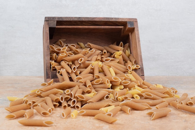 Pilha de massa crua em uma cesta de madeira no espaço de mármore.