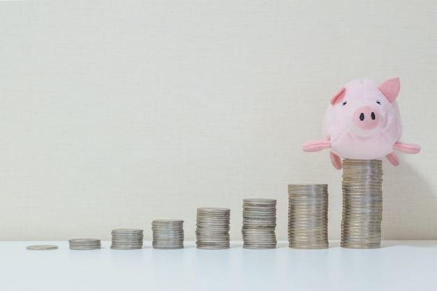 Pilha de moeda começar de baixo para alto com boneca de porco no topo no sucesso de salvar o conceito de dinheiro