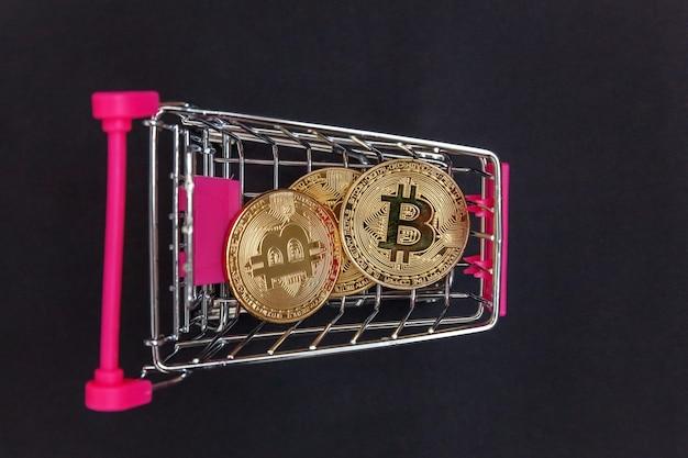 Pilha de moedas bitcoin em um mini carrinho de compras, conceito de mineração