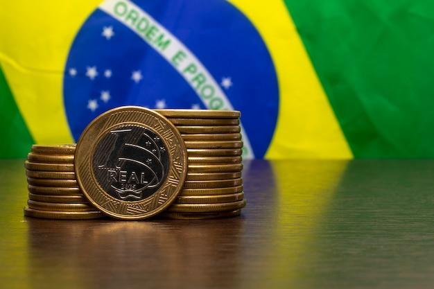 Pilha de moedas brasileiras com um real em destaque e a bandeira do brasil ao fundo