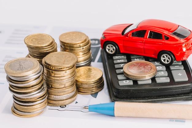 Pilha de moedas; calculadora; carro de brinquedo e caneta no modelo