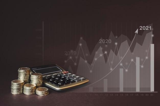 Pilha de moedas, calculadora, estatísticas virtuais de gologram, gráfico com seta para cima. conceito de crescimento de negócios