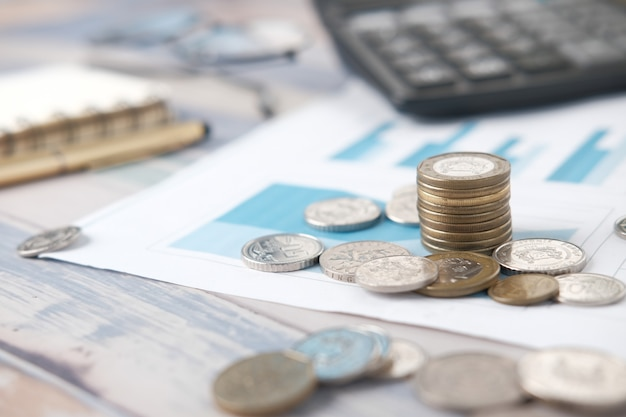 Pilha de moedas, calculadora gráfica financeira e bloco de notas na mesa