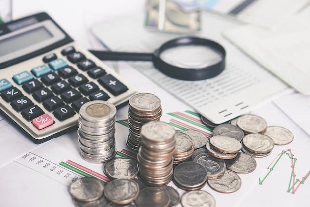 Pilha de moedas, calculadora, lupa na mesa