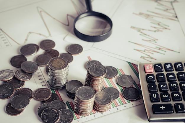 Pilha de moedas, calculadora na mesa