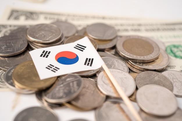 Pilha de moedas com a bandeira da coreia em fundo branco. bandeira em fundo branco. Foto Premium