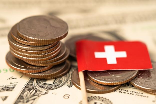 Pilha de moedas com a bandeira da suíça nas notas de eua.