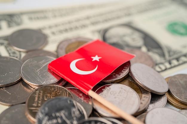 Pilha de moedas com a bandeira da turquia nas notas de dólar dos eua.